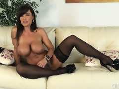 Lisa Ann positions seductively to a pair of stockings and high heels