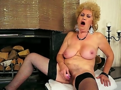 Breasty grandma Effie shoves a new dildo everywhere her shaved pussy everywhere front of the fireplace